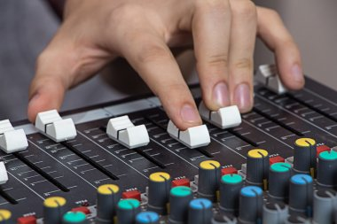 Hands operating sound console