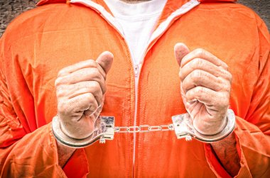 Handcuffed Hands - Guantanamo prison orange clothes