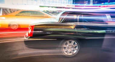 Speeding car and taxi cab in the night traffic of New York City