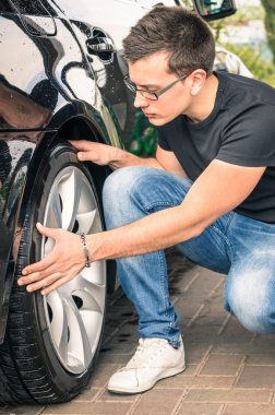 Young man with glasses inspecting a tire of a luxury car before a second hand trade