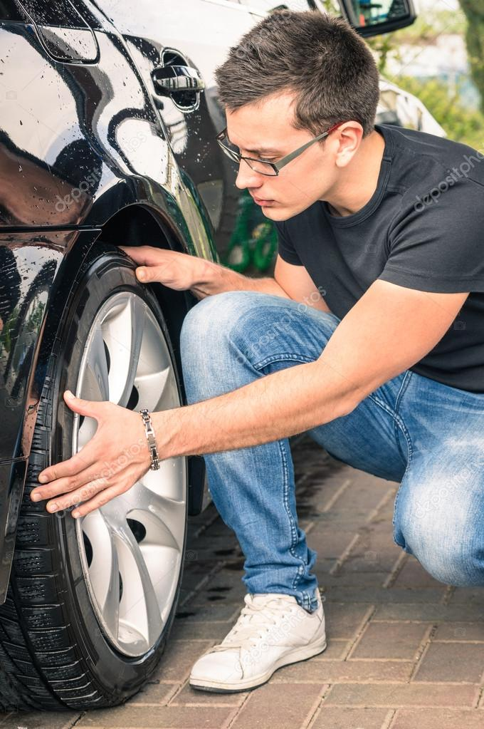 young man with glasses inspecting a tire of a luxury car before a second hand trade stock. Black Bedroom Furniture Sets. Home Design Ideas