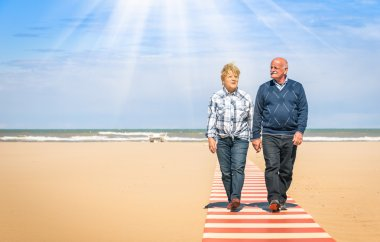 Happy senior couple in love walking hand in hand at the beach - Healthy and joyful elderly lifestyle with man and her wife spending time together outdoors in a sunny day
