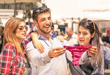 Group of happy young people at the weekly cloth market looking at female underwear - Best friends sharing free time having fun and shopping in the old town in a sunny day