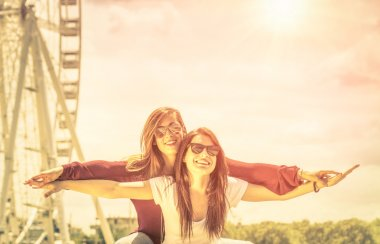 Best friends enjoying time together outdoors at ferris wheel - Concept of freedom and happiness with two girlfriends having fun - Vintage filtered look