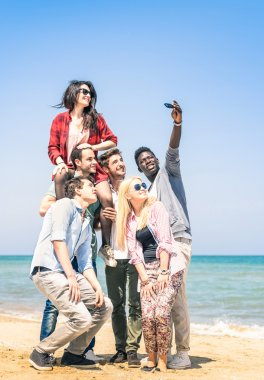 Group of multiracial happy friends taking a selfie at the beach - Concept of international friendship all together against racism