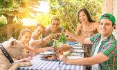 Skupina happy přátel, co jíst a opékání na zahradní gril - pojetí štěstí s mladými lidmi na domácí těší potravin dohromady