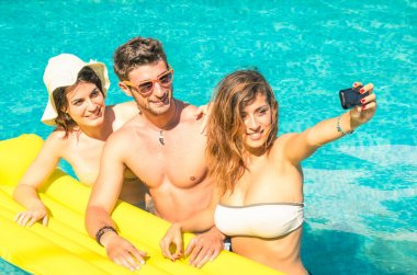 Group of best friends taking selfie at the swimming pool with yellow airbed - Concept of friendship in the summer with new trends and technology - Young man with girlfriends enjoying modern smartphone
