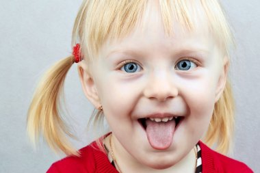 Little girl sticking out her tongue at the camera