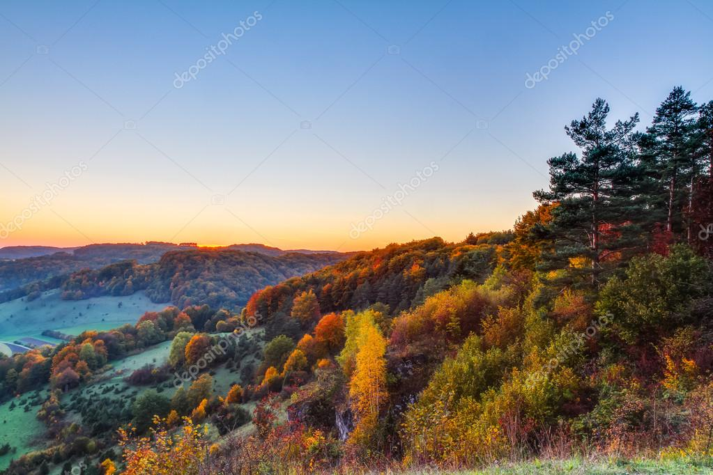Idyllic Autumn Scenery with Colorful Orange Golden Trees near a lovely Country Road in the rocky Jura Mountains of Bavaria, Germany. Sunset in Fall with a wonderful clear sky in the rural countryside.