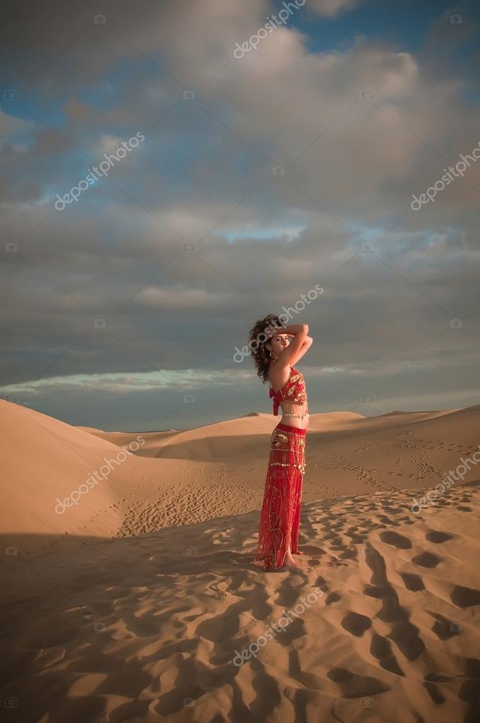Woman belly dancer in desert dunes