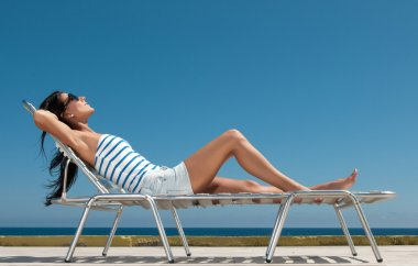 Young beautiful girl in a bathing suit on a sun lounger