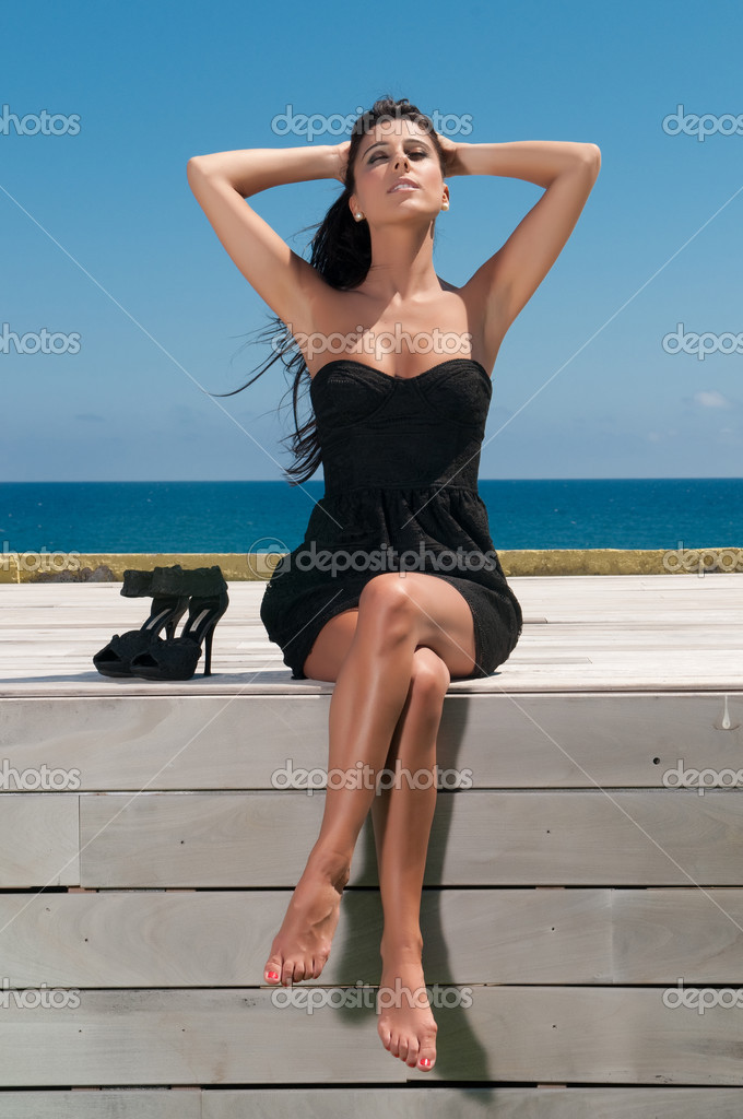 Young Beautiful Girl In A Black Short Dress Sitting On The Beach