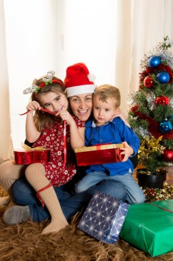 Young Mother in Santa Claus hat with son and daughter