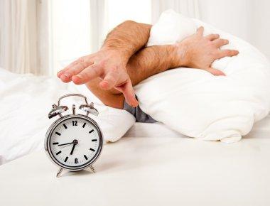 sleeping man disturbed by alarm clock early morning