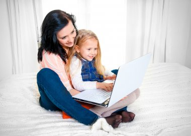 Happy mother and daughter working on computer sitting on bed together