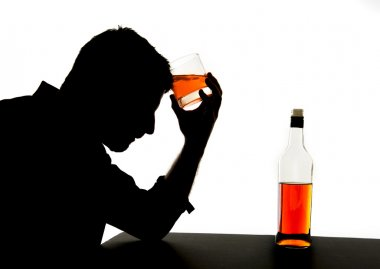 Silhouette of alcoholic drunk man holding whiskey bottle against forehead feeling depressed suffering alcohol addiction and alcoholism problem isolated on White background