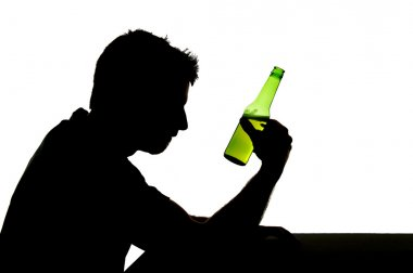 silhouette of alcoholic drunk man drinking beer bottle feeling depressed falling into addiction problem