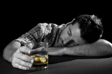 alcoholic man lying drunk with whiskey glass in alcohol addiction and alcoholism concept