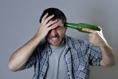 Crazy man holding beer bottle as a gun with handgun pointing to his head