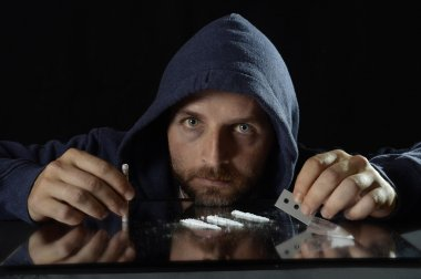 Young drug addict man on hood alone sniffing and snorting cocaine lines with rolled banknote on mirror
