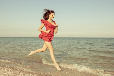 Young woman runs in red dress on the sea