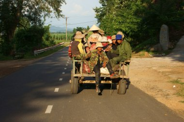 Farmer move by Cong Nong (farm vehicle) on road under golden light
