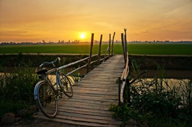 Bicycle on wooden fence of bridge at sunset
