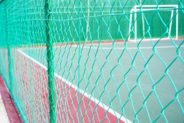 Green colored chain link fencing surrounding futsal court.