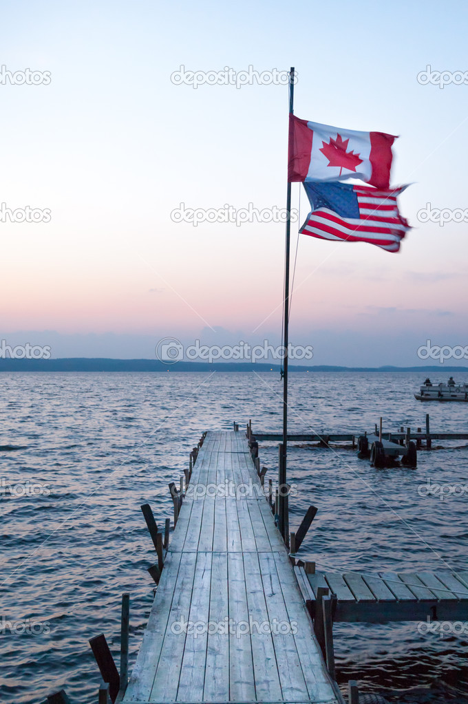 Canadian and American flags at a dock — Stock Photo