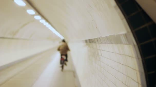s kapucí cyklista mizí v tunelu v pomalém pohybu