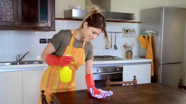 mladá hospodyňka čištění nábytku v kuchyni
