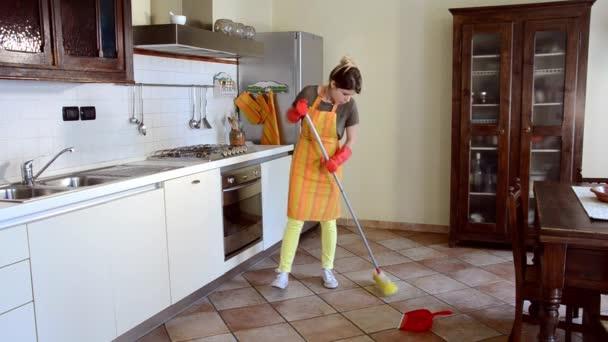 junge Frau putzt den Küchenboden
