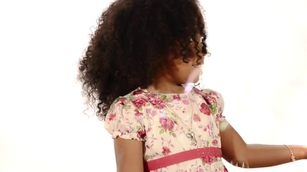 Funny mixed race black and latino brazilian little girl isolated with bubbles floating