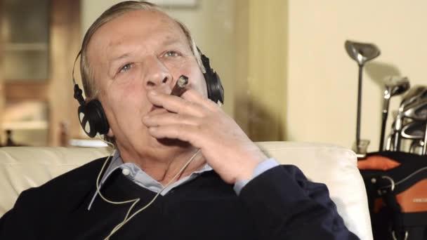 starší muž kouří doutník a poslechu hudby