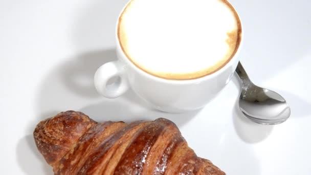 croissanty a cappuccino na bílé plotně otočení.