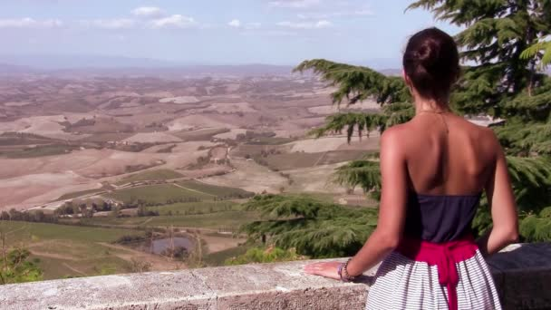 Young tourist observing a tuscan landscape