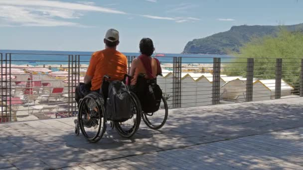 Couple at the beach with wheelchairs