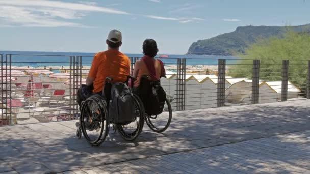 pár na pláži s invalidních vozíků