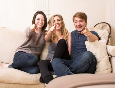 Group of happy teenagers on a sofa pointing