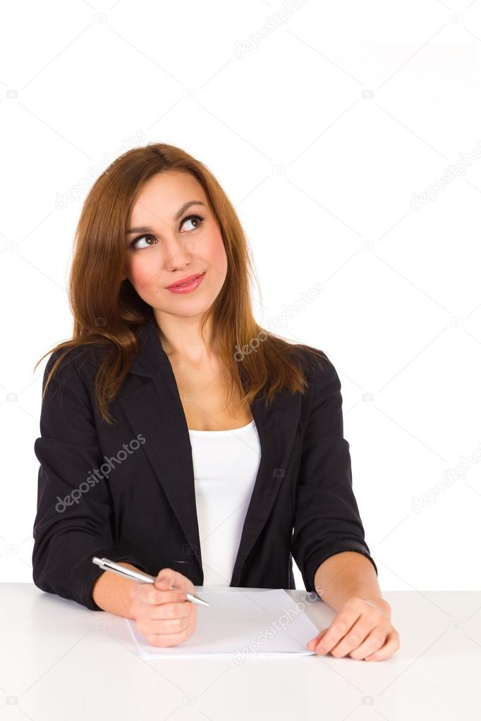Beautiful young woman sitting at the desk and thinking.