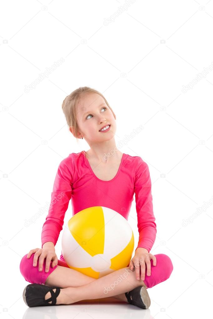 Small gymnastics girl with a ball looking away