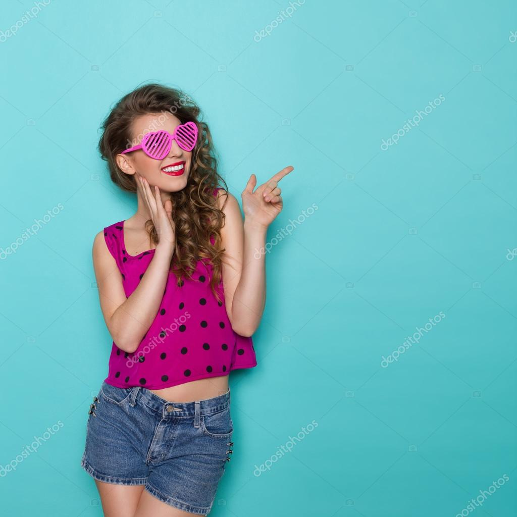 Smiling girl in heart shaped glasses is pointing
