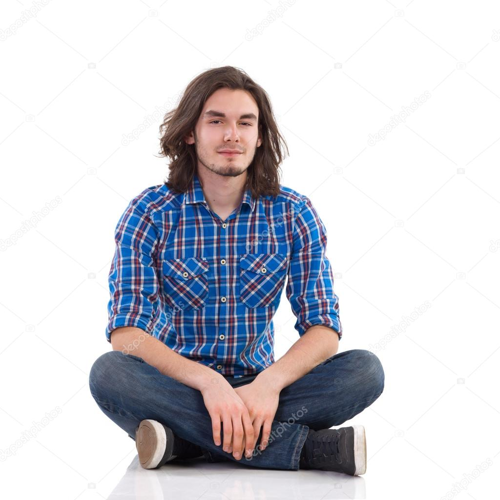 Cheerful young man sitting on the floor with legs crossed.