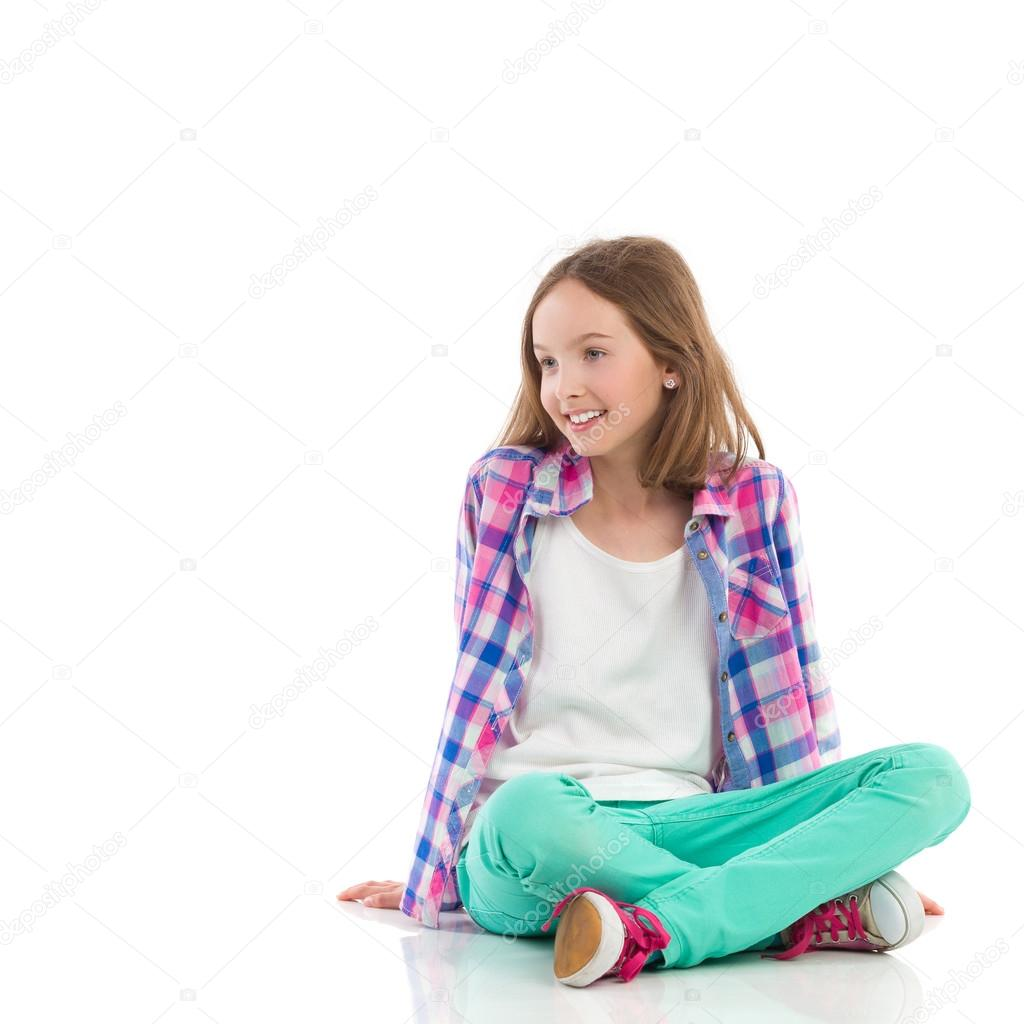 Smiling girl sitting with legs crossed