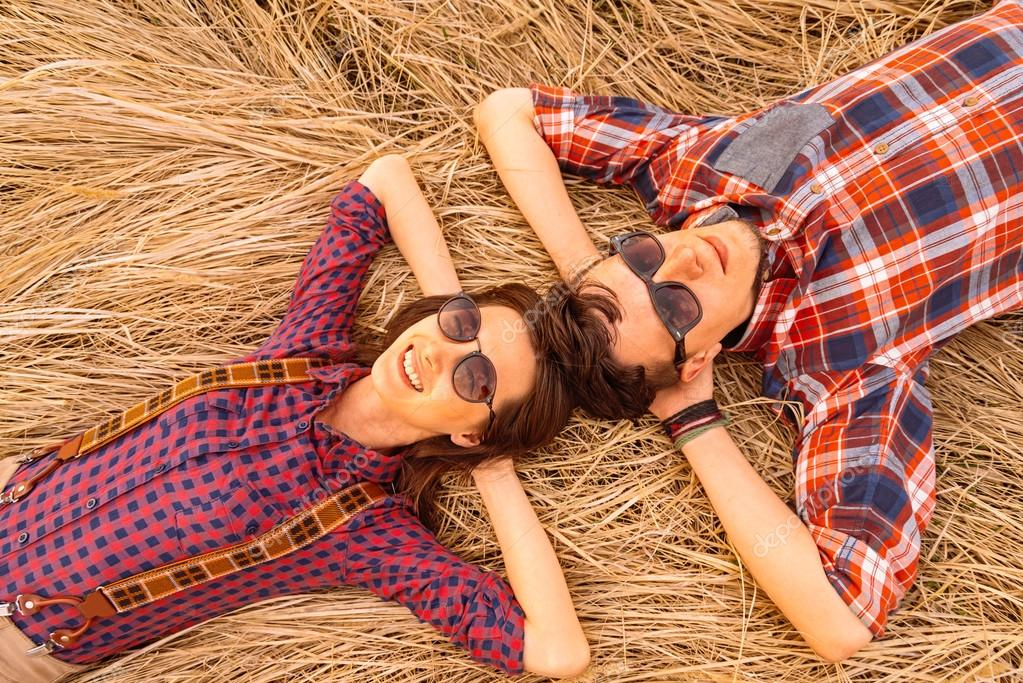 Young couple rests on dry grass