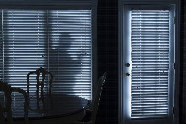 Silhouette of Burglar Sneeking Up To Backdoor At Night