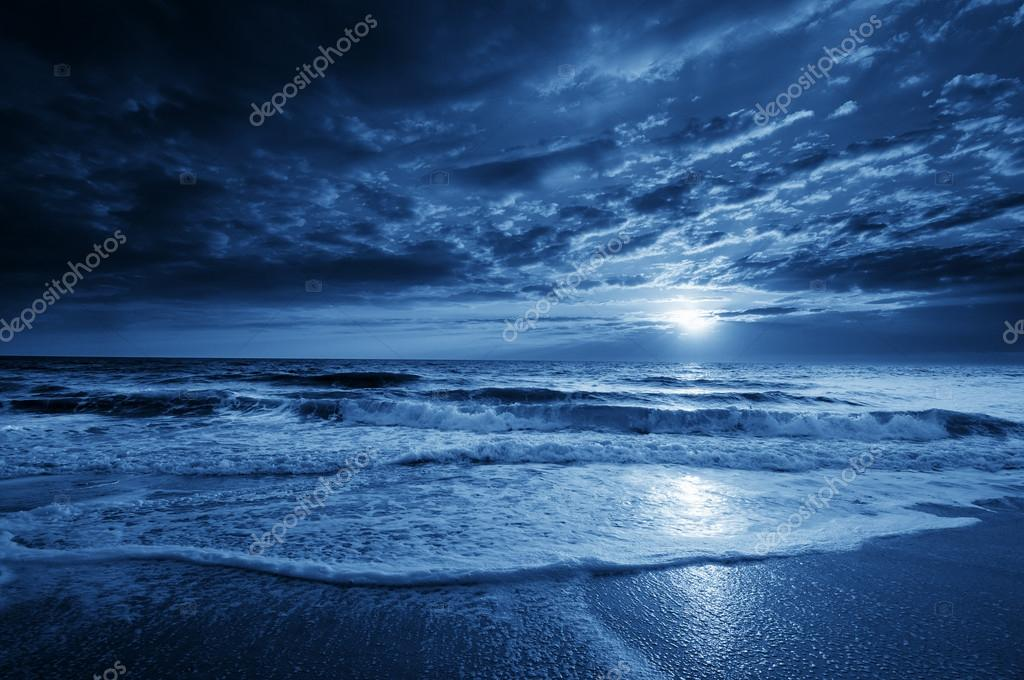 Midnight Blue Coastal Moonrise With Dramatic Sky and Rolling Waves