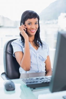 Cute businesswoman calling someone with her mobile phone