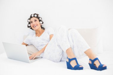 Happy brunette in hair rollers and wedge shoes using her laptop on bed