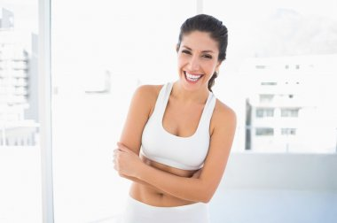 Fit laughing woman in sportswear with arms crossed looking at camera